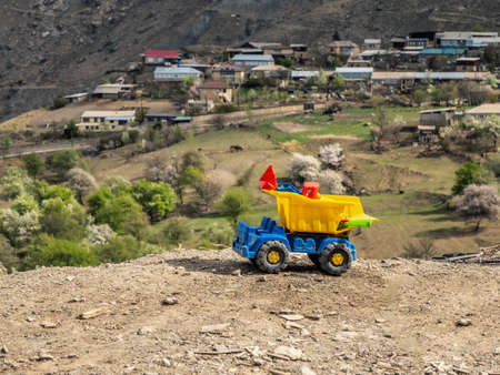 Toy yellow dirty dump truck on the background of a mountain landscape.