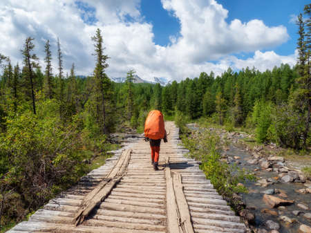 A male tourist with a large orange backpack walks along an old wooden bridge against the background of a coniferous forest and mountains in the distance