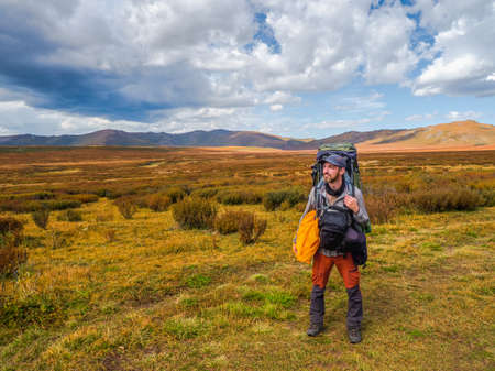 Tired tourist with a large backpack and bags on the sides of his body happily looks into the distance against the background of black dramatic clouds against the background of tundra mountains.