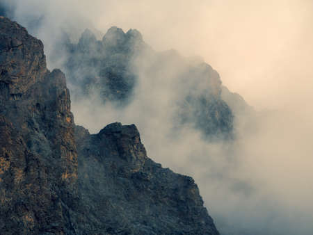 Soft focus. Horror mountain shadows. Dramatic fog among giant rocky mountains. Ghostly atmospheric view to big cliff. Low clouds and beautiful rockies. Minimalist scenery mysterious place.