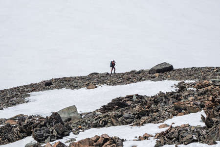 Winter hiking in the snow-capped mountains. Highland scenery with sharpened stones of unusual shape. Awesome scenic mountain landscape with big cracked pointed stones among snow in sunlight.