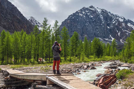 A photographer on an old wooden bridge takes pictures of distant mountains. Stunning view of the mountain valley under the blue sky. Aktru. Altai mountains.