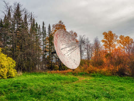 Vintage Radio Telescope, a large satellite dish on a background of observation forest and cloudy sky, radar in the past. Technology concept, search for extraterrestrial life, wiretap of space.