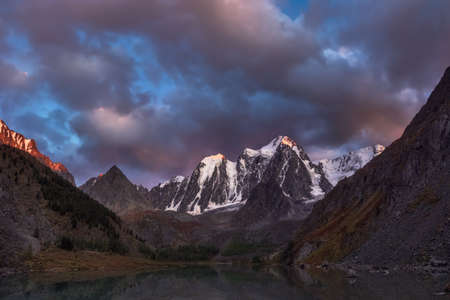 Darkness mountain landscape with great snowy mountain lit by dawn sun among dark clouds. Awesome alpine scenery with high mountain pinnacle at sunset or at sunrise. Big glacier on top in orange light. Stock Photo