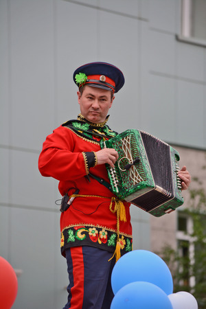 cantal: Mirny, Russia - June 12, 2014: Accordion player in national Russian clothes in celebration of the Day of Russia in the city of Mirny, Republic of Sakha