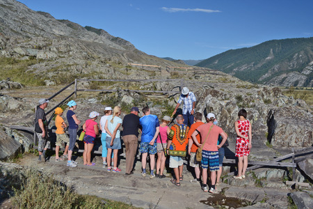 Altai, Russia - August 23, 2014: Tour of tourists in the tract Kalbak Tash view petroglyphs. Redakční