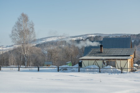 Winter rural landscape in Siberia. The village in the Altai mountains. Panorama HDR - high dynamic range.