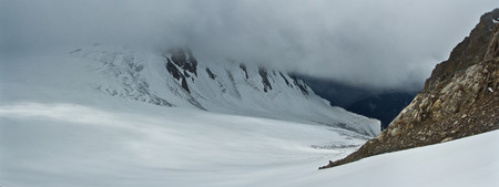 Snow mountains in the clouds, panorama in Altaj, Russia  at the summer