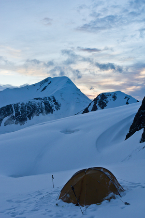 Beautifull view to snow mountains and tent on the glacier in Altaj, Russia  at the summer
