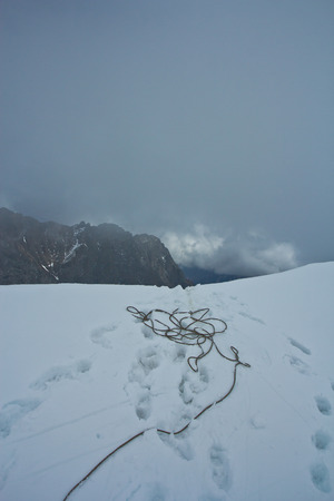 Rope for climbintg and steps of climbers in the top of snow mountain in bad wether in Altaj, Russia  at the winter