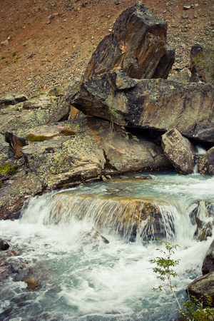 Small waterfall on the stream in the stones in Altaj, Russia  at the summer