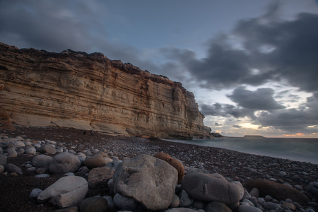 Sunset on the coast  with blue clouds  near rocks in the Cyprus near Paphos  at the winter