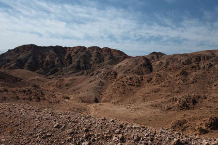 Way in the desert  in the Israil in sunny day with red mountains, green trees and blue sky near Eilat