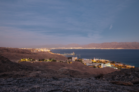 Veiw from mountains to israil and iordan mountains near  of Eilat city in the desert  in the evening sunset  with blue sky and city lights