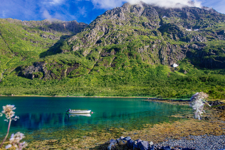 White boat on the shore of turquoise lake with view to green  mountains in the Norway at summer time