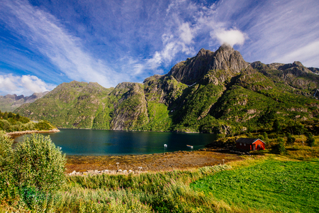 Red house on the shore of turquoise lake with view to green  mountains in the Norway at summer time Reklamní fotografie