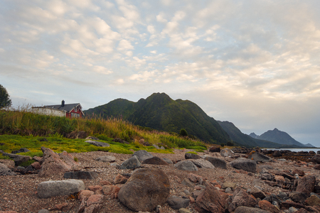Red house on the shore with view to mountain and sunset on the sea in the Norway, lofoten islands at summer time with stones on the beach Reklamní fotografie