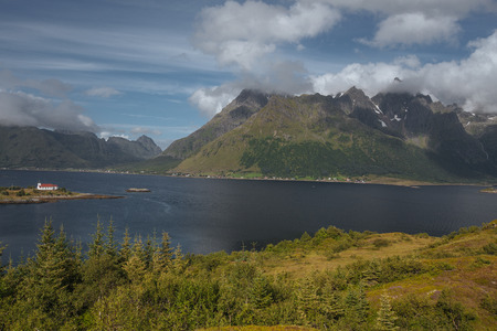 House on the shore with view to mountain and sea in the Norway, lofoten islands at summer time with forest on the hill