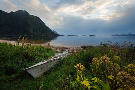 White boat on the shore with view to mountain and sea in the Norway, lofoten islands at summer time with sunset