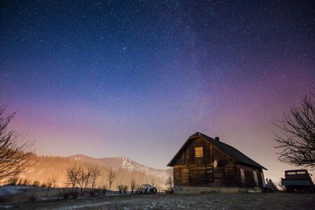 Abandoned house at night with stars and milky way in the Carpatian mountains