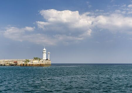 White lighthouse on the pier in the city of Yalta, Republic of Crimea, Russia. Stock photo.