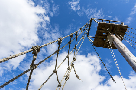 rope ladder: Old rope ladder and mast against cloudy sky