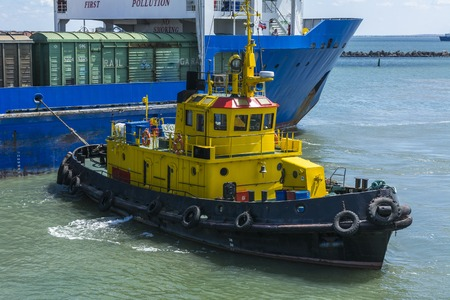 escorted: A yellow tugboat assisting a large cargo ship Stock Photo