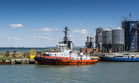 maneuvering: Tugboat moored in the port Stock Photo