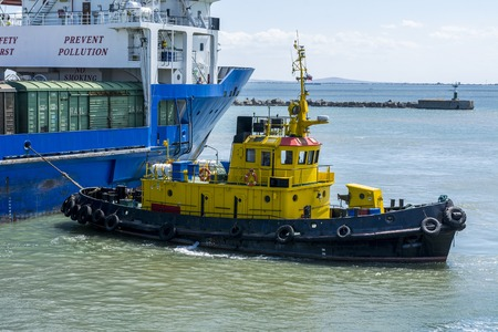 A yellow tugboat assisting a large cargo ship. Stock photo.