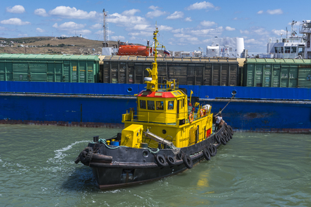 escorted: A yellow tugboat assisting a large cargo ship. Stock photo.