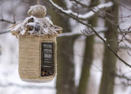 Vintage bird feeders. Handmade. Bird feeder covered with snow. Small depth of field.