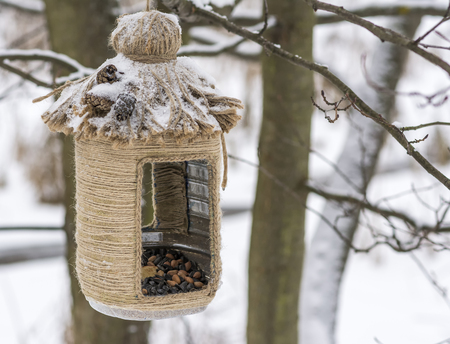 woodpecker: Vintage bird feeders. Handmade. Bird feeder covered with snow. Small depth of field.