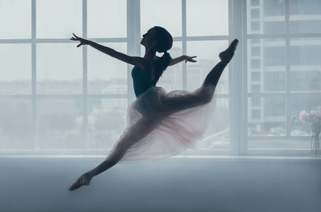 Ballerina in a transparent dress is jumping in front of a window
