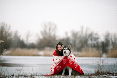 Girl with alaskan malamute dog wrapped  in white-red blanket. They sit over winter lake. Stock Photo