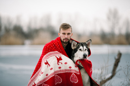 Young man with alaskan malamute dog wrapped  in white-red blanket. They sit over winter lake.