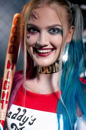 prank: Portrait of smiling girl in costume Harley Quinn with crazy eyes. She stands with bat. Close up. Cosplay. Stock Photo
