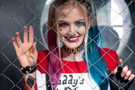garb: Portrait of smiling girl in costume Harley Quinn. She looks through the grid. Close up. Cosplay.