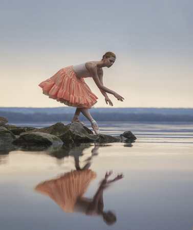 Ballerina in ballet pose above lake on background of sky. Her reflection can be seen In water.