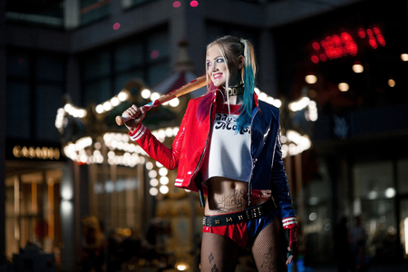 female face closeup: Smiling cosplayer girl in costume Harley Quinn on background lights of night city. Cosplay Stock Photo