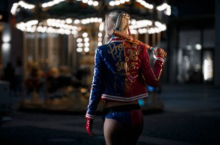 cosplay: Cosplayer girl in costume Harley Quinn on background lights of night city. Cosplay