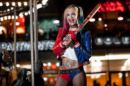 harley: Portrait of smiling cosplayer girl in costume Harley Quinn on background lights of night city. Cosplay