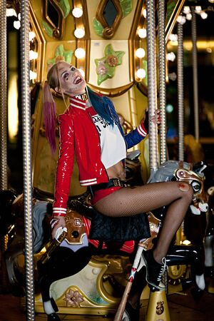 harley: Smiling cosplayer girl in costume Harley Quinn on background lights of carousel ride. Cosplay Stock Photo