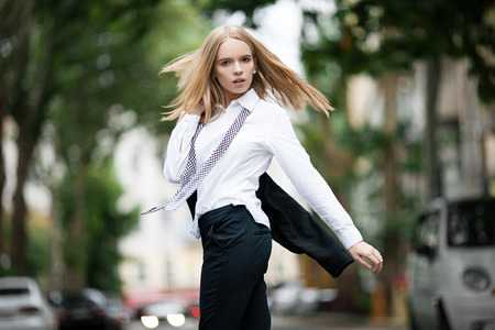Girl in shirt and tie on city street. She threw back her jacket and her hair fly apart. Stock Photo
