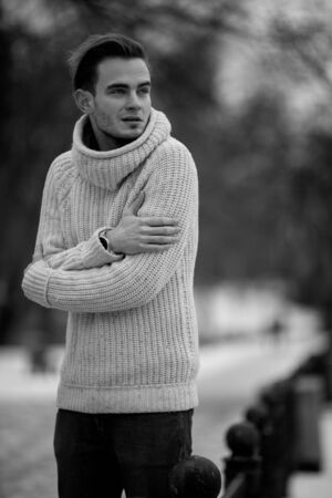 black sweater: Young man in cold winter weather. He is cold, and he shrank from the cold. Stock Photo