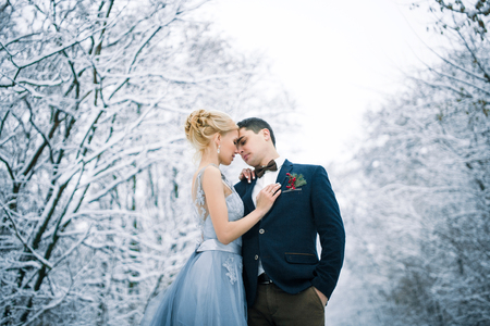 Bride and groom among snowy forest. They are standing and hugging.  Winter wedding outdoors. Close up. Zdjęcie Seryjne