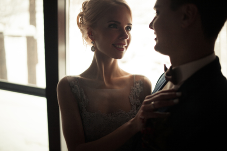 tenderly: Portrait of smiling bride and groom on window background. Bride is smiling and tenderly looks at groom. Stock Photo