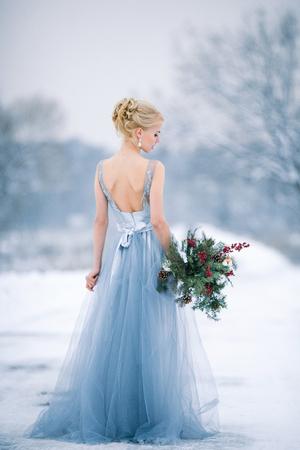 雪の風景の中で花嫁。彼女が立っています。 バックからの眺め。冬の結婚式の屋外。
