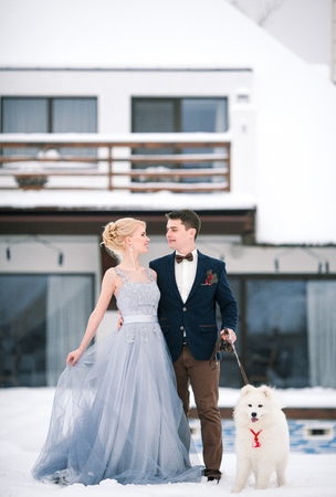 tenderly: Bride and groom in winter with dog malamute on snow and home background. Groom hugging bride and they tenderly look against each other.