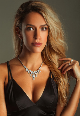Suntanned girl portrait in a bra-top and necklace on gray background. She stands. Stock Photo
