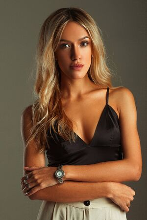 suntanned: Suntanned girl portrait in bra-top, pants on gray background. She stands and crossed her arms. On her arm there are watch and rings. Stock Photo